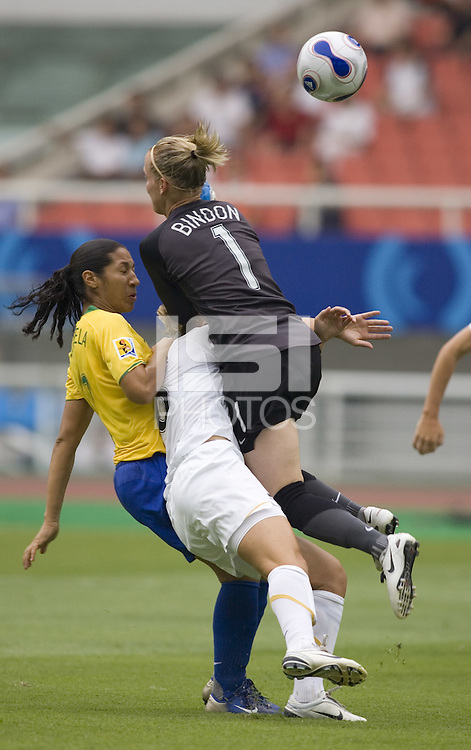 Brazil midfielder (7) Daniela collides with New Zealand goalkeeper (1) Jenny Bindon and defender (6) Rebecca Smith during their first round game at the 2007 FIFA Women's World Cup at Wuhan Sports Center Stadium in Wuhan, China.  Brazil defeated New Zealand, 5-0.