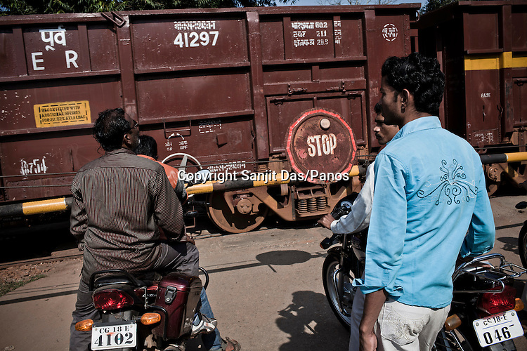 Traffic waits at the railway crossing while a 57-carriage train pulled by 3 engines carrying iron ore passes by Dantewara town in Chhattisgarh, India. Photo: Sanjit Das/Panos for The Times