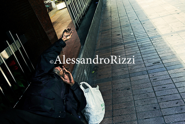 Homeless man lying on bench
