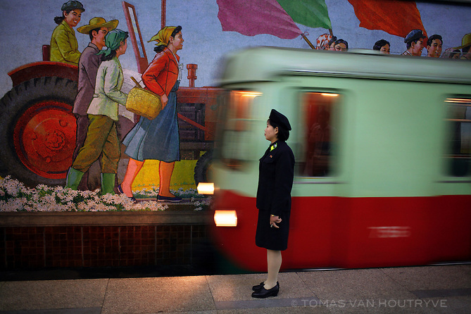 An attendant stands near the tracks as a metro train arrives in the station in the subway of Pyongyang, North Korea (DPRK) on 20 August 2007.