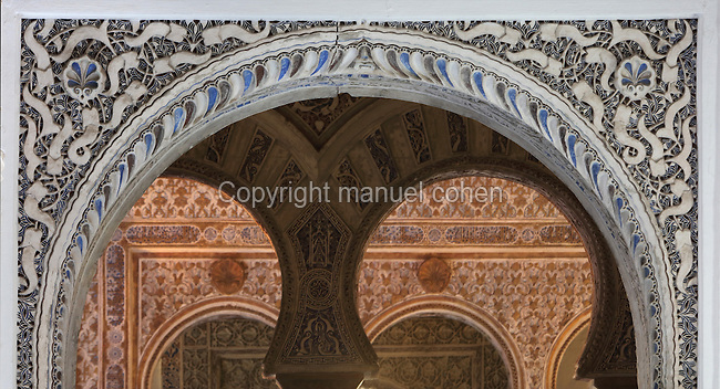 Arch at the entrance to the Salon de Embajadores, or Hall of Ambassadors, in the Mudejar Palace, or Palacio del Rey Don Pedro, built by Pedro I of Castile in 1364, in the Real Alcazar, a Moorish royal palace in Seville, Andalusia, Spain. The Hall of Ambassadors was the throne room of King Don Pedro I, 1334-1369. It is a square room with a wooden dome covered in star patterns, added in 1427. The Alcazar was first founded as a fort in 913, then developed as a palace in the 11th, 12th and 13th centuries and used by both Muslim and Christian rulers. The Alcazar is listed as a UNESCO World Heritage Site. Picture by Manuel Cohen