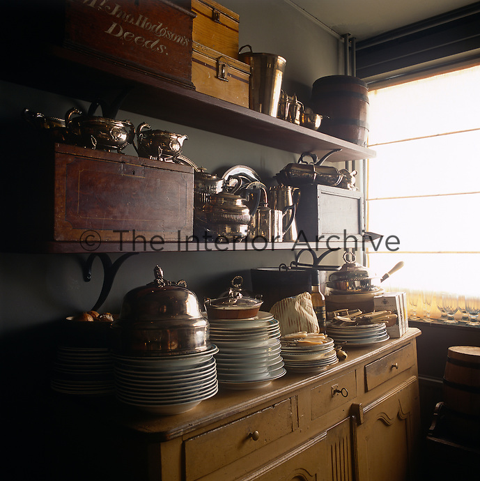 Silverware and boxes are arranged on wall shelves above stacks of plates crowded on a sideboard top.
