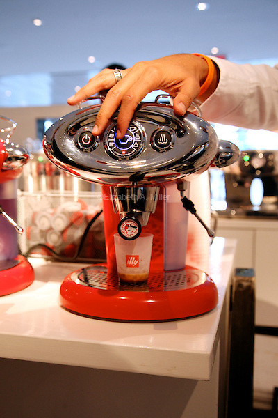 "An Illy employee makes an espresso for a customer in Illy Coffee's ""Green"" Push Button House, on display at the Time Warner Center.  Designed by Adam Kalkim, the mobile exhibit is a fully functional and sustainable five-room home on display to promote Illy's new Hyper Espresso system of coffee extraction."
