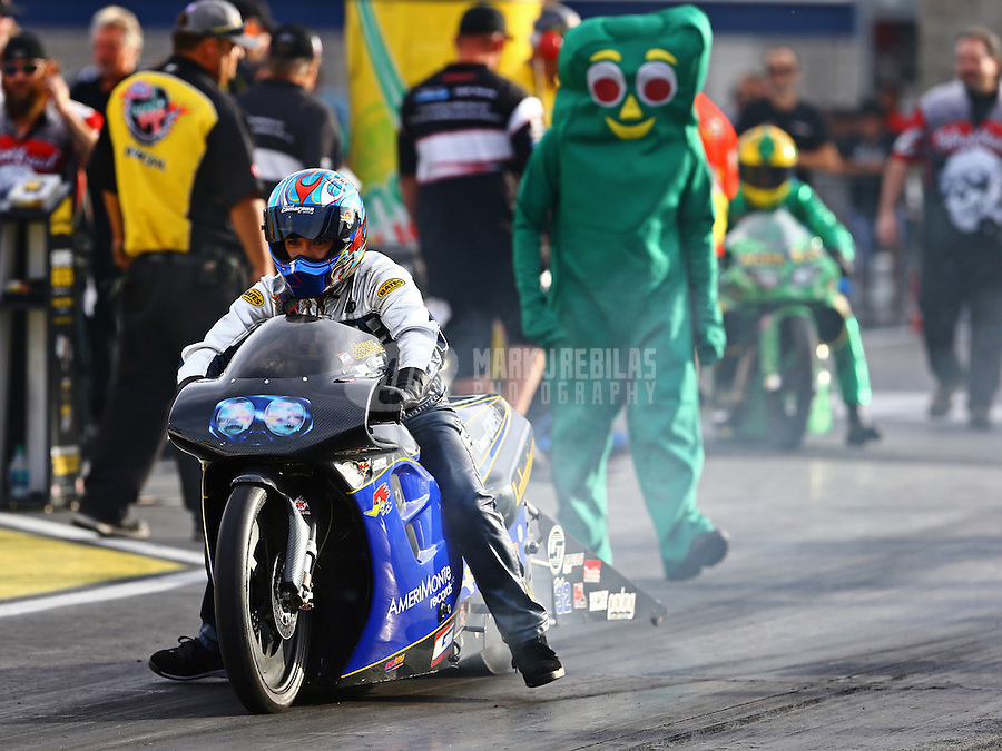 Oct 31, 2014; Las Vegas, NV, USA; A crew member wears a Gumby costume for Halloween as he watches NHRA pro stock motorcycle rider Freddie Camarena do a burnout during qualifying for the Toyota Nationals at The Strip at Las Vegas Motor Speedway. Mandatory Credit: Mark J. Rebilas-USA TODAY Sports
