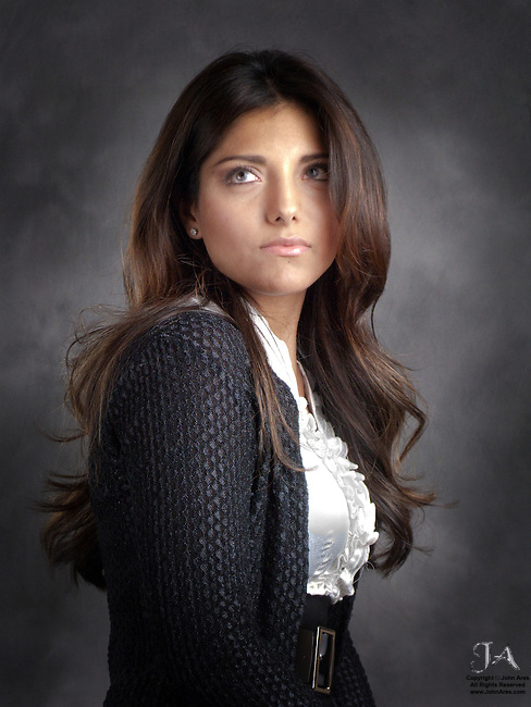 Studio Portrait of Beatriz Carranza.  With a pensive look and Long brunette hair.  White frilly blouse and black sweater.