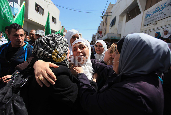 Palestinians mourn during the funeral of Hamza Abu Al-Heja, 20, a member of the military wing of Hamas, the Ezzedine al-Qassam Brigades in the northern West Bank city of Jenin on March 22, 2014 after he was killed alongside two other Palestinians during an operation launched by Israeli soldiers in the Jenin refugee camp to arrest a militant. Medical and security sources said that two of those killed were militants and the third was a civilian. Photo by Issam Rimawi