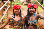 Two indigenous Embera women dressed up for visitors in her village on Lake Alejuela in Panama.  One girl's body is painted with the juice of the jagua berry to make a temporary tattoo.  It takes about two weeks to wear off.  The women's tops are beaded and often decorated with silver coins. Chagres National Park