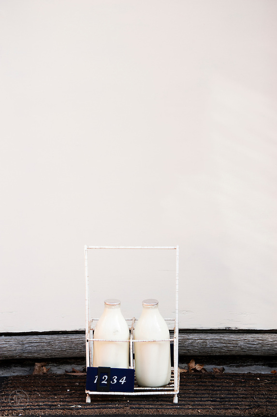 Glass bottles of freshly delivered milk wait on a doorstep in the early morning.
