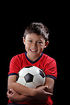 Boy with soccerball on black backgound with dramatic lighting style