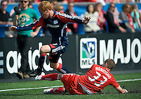23 May 09: New England Revolution midfielder/defender Jeff Larentowicz #13 jumps to avoid a sliding tackle from Toronto FC midfielder Carl Robinson #33 during a game between the New England Revolution and Toronto FC.Toronto FC won 3-1.