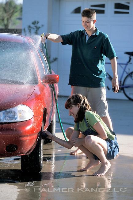 Teen couple washing a car