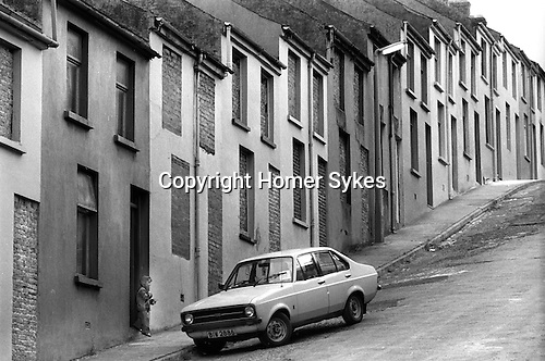 Derry, Northern Ireland. 1979<br /> One family remains in this Waterside street; houses area abandoned and boarded up as families have moved away due to sectarian violence.<br /> <br /> For those that like to know these things I am advised this is a Ford Escort Mk2.