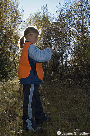 Young girl hunter holding shot ruffed grouse