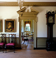 The doorway leading to the drawing room is flanked by an antique grandfather clock and an oil painting