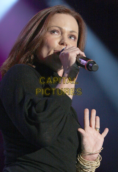 "BELINDA CARLISLE.Former lead singer of the Go-Go's, Belinda Carlisle, performed as part of the ""Regeneration Tour"" at Chastain Park, Atlanta, Georgia, USA, .August 29, 2008..live music in concert gig half length black top blouse trousers microphone hand  bangles bracelets .CAP/ADM/DH.©Dan Harr/AdMedia/Capital Pictures"
