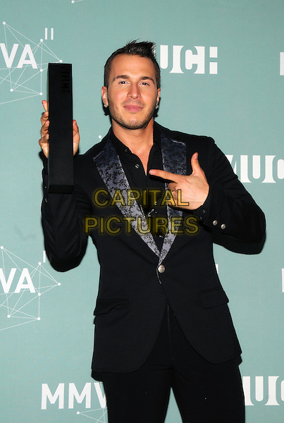 Shawn Desman  .Shawn Desman poses in the press room at the 22nd Annual MuchMusic Video Awards at the MuchMusic HQ, Toronto, Ontario, Canada..half length black suit jacket winner trophy stubble facial hair hand pointing .CAP/ADM/BPC.©Brent Perniac/AdMedia/Capital Pictures.