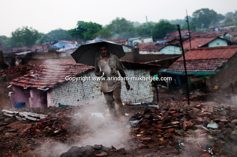 A man takes a shortcut through the rubble of a house at Indra chowk. Indra Chowk located at the border of Jharia town has also been affected by the mine fire. Even some 10 years ago the fire hadn't spread to the buildings at the area like now. A huge coal mine fire is engulfing the city of Jharia from all its sides. All scientific efforts have gone in vain to stop this raging fire. This fire is affecting lives of people living in and around Jharia. Jharkhand, India. Arindam Mukherjee