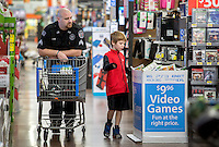STAFF PHOTO JASON IVESTER --12/09/2014--<br /> Benton County Sgt. Jorge Keene walks with Dylan Williams, 10, of Bentonville while shopping for clothes and toys on Tuesday, Dec. 9, 2014, inside the Wal-Mart Supercenter on Pleasant Crossing Boulevard in Rogers. Members of the Benton County Sheriff's Office helped the children pick out clothes and toys with a $150 budget each as part of the department's annual Shop With a Cop program.