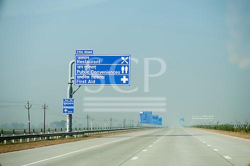 Uttar Pradesh, India. Agra to Delhi; Yamuna Expressway. Empty motorway with new blue bi-lingual signs in English and Hindi. Toll sign.
