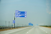 Uttar Pradesh, India. Agra to Delhi; Yamuna Expressway. Empty motorway with new blue bi-lingual signs in English and Hindi. Toll sign.