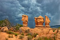 792800273 lightning flashes behind the four trolls red rock formations during a summer thunderstorm in devils garden escalante grand staircase national monument utah united states