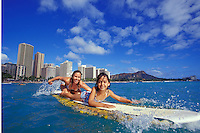 Mother and daughter surfing together off Waikiki, Diamond Head in background, Oahu, Hawaii