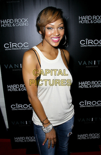 MEGAN GOOD .grand opening of Vanity Nightclub at Hard Rock Hotel and Casino, Las Vegas, Nevada, USA, .2nd January 2010..half length jeans white vest top ripped denim destroyed distressed black smiling hoop earrings bra straps showing .CAP/ADM/MJT.©MJT/Admedia/Capital Pictures