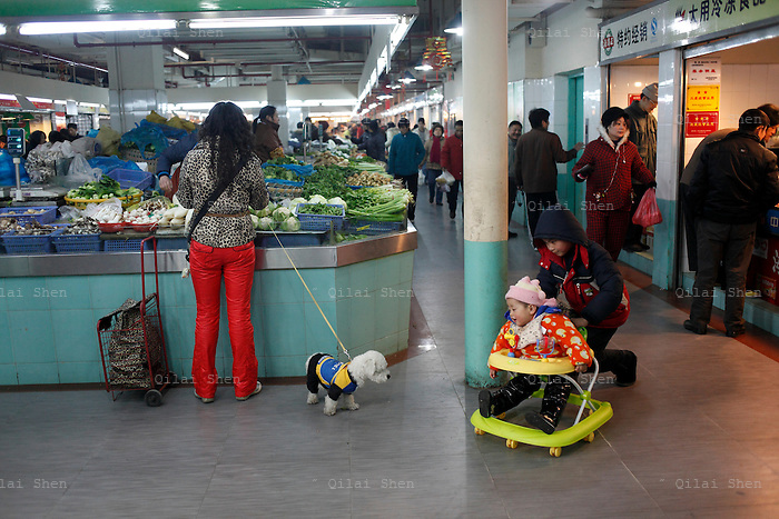 A boy pushes his brother's walker in a market in Shanghai, China on 26 January, 2009.  Despite the one-child-policy, some rural families, with lax enforcements, have two or more children regardless.