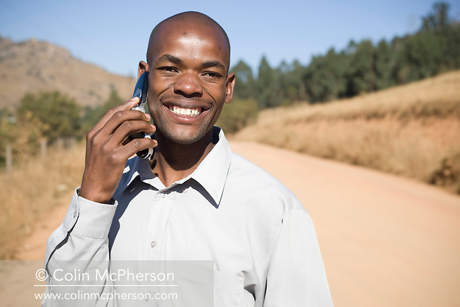 A Swazi man using a mobile telephone outside his smallholding in Pine Valley, Swaziland. The Kingdom of Swaziland (population 1.1m), a small, landlocked country in southern Africa was bordered by South Africa on three sides and Mozambique to the east, with Mbabane as its administrative capital. At the start of the 21st century, the country had the highest incidence per head of population of HIV/Aids in the world and and high levels of poverty mainly in rural areas where 75 per cent of the population lived.