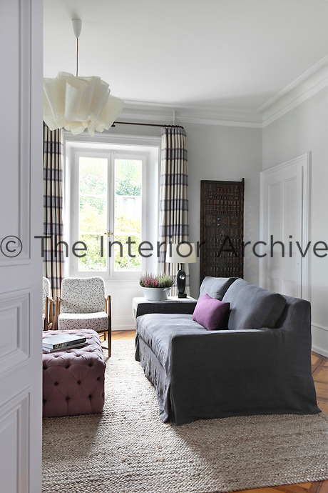 An African carved panel   adds an interesting feature to a wall of this pale grey sitting room
