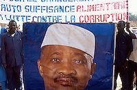 Mali. Province of Segou. Niono. October 16 2003. Worlwide food day.  The crowd waits for the arrival of the malian president Amadou Toumani Toure (ATT). Two men holds a poster (image) from the president and some political slogan about the fight against corruption and for a self-sufficient world foodproduction campaign. © 2003 Didier Ruef