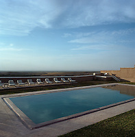 A row of sun-loungers line one side of the swimming pool which has dramatic views over the surrounding landscape