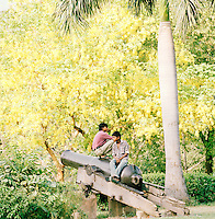 Two boys sit on an old canon, The Residency, Lucknow, Uttar Pradesh, India