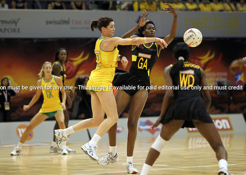 09.07.2011 Australia's Sharni Layton and Jamaica's Romelda Aiken in action during the netball match between Jamaica and Australia at the Mission Foods World Netball Championship 2011 held at the Singapore Indoor Stadium in Singapore . Mandatory Photo Credit ©Michael Bradley.