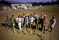 August 21, 2001-Dili, East Timor- Workers spread coffee parchment out on tarpaulins to dry in the tropical sunshine, and then need to turn the coffee every half hour until it reaches a moisture content of about 12%. This photo is taken at one of the Cooperativa Café facilities in the Tibar area to the west of Dili.  Photograph by Daniel J. Groshong/Tayo Photo Group