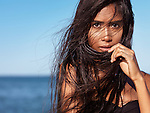 Expressive portrait of a beautiful young woman with long wet dark hair blown in the wind with sea in the background.