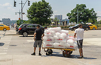 Deliverymen with a supply of bagged ice destined for a bar in New York on Saturday, June 25, 2016. (© Richard B. Levine)