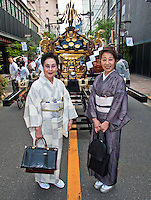 Two ladies in kimono`s pose infront of portable shrine at local festival,