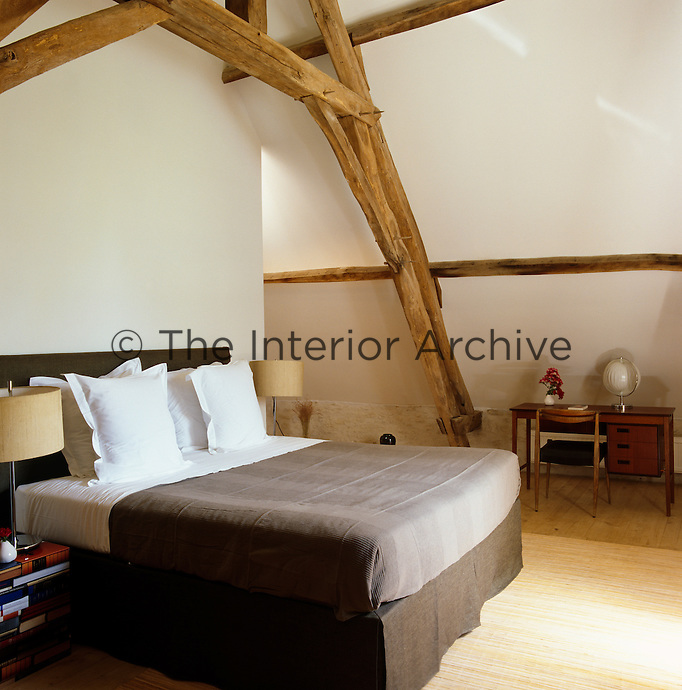 The attic bedroom has a neutral colour palette with a bed covered in chocolate brown linen