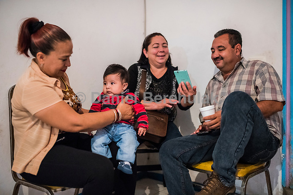 Vicky Delgadilo, holds her grandson Vicente, 4 months, as Carlos Saldaña talks iwht his sister María Isabel Saldaña Grajales during a birthday party for their grandson, Hector Yael, 10, at a family gathering at Vicky's daughter, Cinthia Hernández Delgadilo's house in Xalapa, Mexico on November 4, 2017. <br /> Photo Daniel Berehulak for The New York Times
