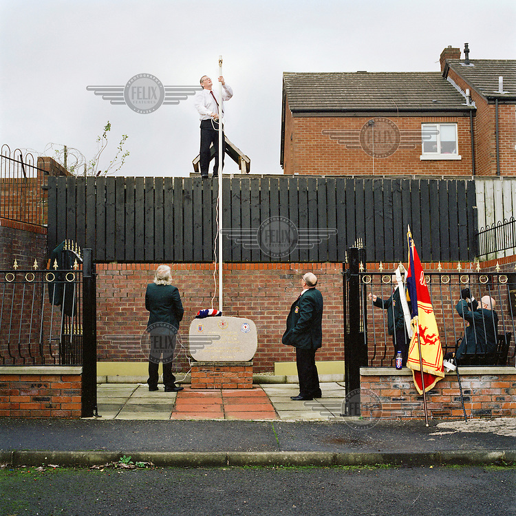 Members of the North Belfast battalion of the Ulster Defence Association (UDA)  prepare to raise the symbolic Union Jack flag at the Tiger's Bay estate for the Remembrance Sunday service in 2011. This yearly gathering brings together the current active members of the organisation and those who have stepped down. All gather to pay respects to friends and family lost through acts of violence during 'The Troubles', a period of intercommunal violence and strife which lasted for approximately 3 decades from the 1960s to 1998, when the Good Friday Agreement ended outright hostilities.