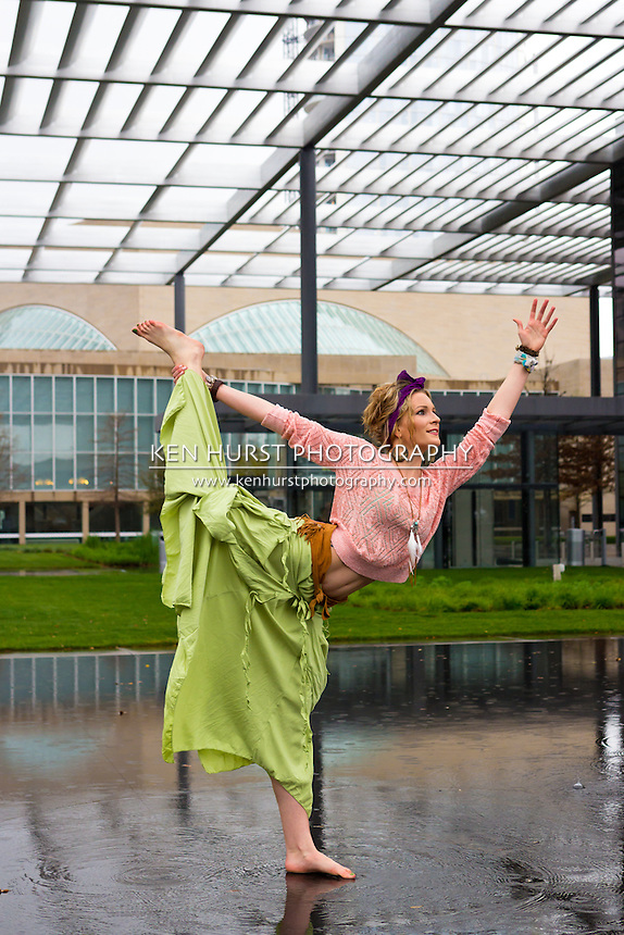 Beautiful woman dressed in Bohemian style colorful clothing practicing yoga in the reflecting pool at the Winspear Opera House in Dallas, Texas.