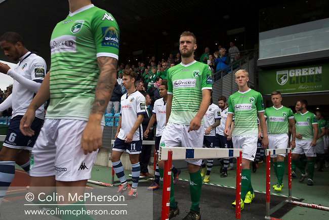 The two players walking on to the pitch before kick-off as Guernsey (in green) take on Corinthian-Casuals in a Isthmian League Division One South match at Footes Lane. Formed in 2011, Guernsey FC are a community club located in St. Peter Port on the island of Guernsey and were promoted to the Isthmian League Division One South in 2013. The visitors from Kingston upon Thames won the fixture by 1-0, watched by a crowd of 614 spectators.