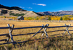 Park County, MT: Wood fence line and barn in an open meadow in fall