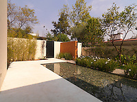 A Zen-like pebble-bottomed pool is the focus of the well manicured front garden of this modern home