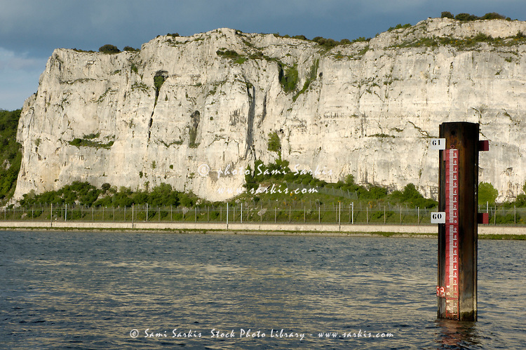 Water level of the Rhone River is measured with dramatic cliffs in the background, Drome, France.