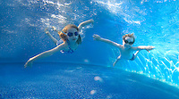 Two Young Children swimming underwater