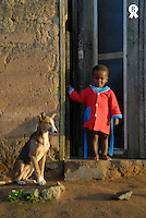 Girl (2-3) standing by dog at house entrance, portrait (Licence this image exclusively with Getty: http://www.gettyimages.com/detail/200503595-001 )