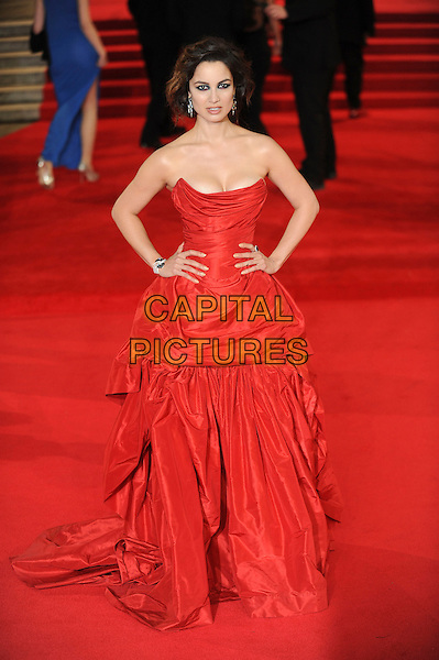 Berenice Marlohe.'Skyfall' Royal World Film Premiere, Royal Albert Hall, Kensington Gore, London, England..23rd October 2012.full length red strapless dress cleavage gathered hands on hips.CAP/CAS.©Bob Cass/Capital Pictures.