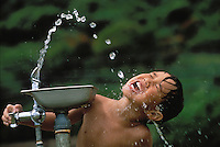 Young local boy drinking water from a fountain.